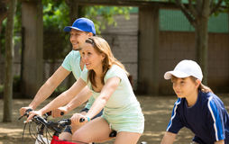 Happy family of three cycling on city road Stock Images