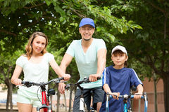 Happy family of three cycling through city Royalty Free Stock Images