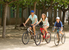 Happy family of three cycling on street road Stock Photo