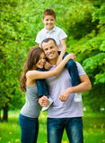 Happy family of three. Dad keeps son on shoulders Stock Photos