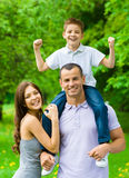 Happy family of three. Daddy keeps son on shoulders. Happy family of three. Dad keeps son on shoulders. Concept of happy family relations and carefree leisure royalty free stock photo