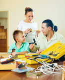 Happy family of three doing something with  tools Royalty Free Stock Photography