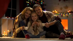 Happy family of three drinking hot cocoa near Christmas tree, miraculous day. Stock photo stock photos