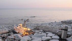 Happy family enjoying summer sunset on wild beach around bonfire.