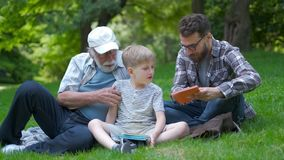 Happy family of three generation - father, grandfather and blond son sitting on grass at park with books learn to read
