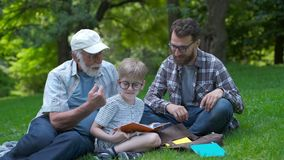 Happy family of three generation - father, grandfather and blond son sitting on grass at park with books learn to read stock video