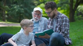 Happy family of three generation - father, grandfather and blond son sitting on grass at park with books learn to read stock video footage