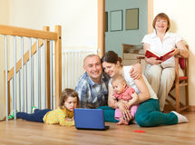Happy family of three generations using blue laptop  in home int Royalty Free Stock Images