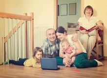 Happy family of three generations using blue laptop  in home int Stock Image