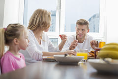 Happy family of three having breakfast at table Royalty Free Stock Photos