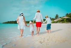 Happy family with three kids walk on beach. Vacation at sea stock image