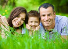 Happy family of three lying on grass. Concept of happy family relations and carefree leisure time stock image
