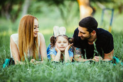 Happy family of three lying on grass. Concept of happy family relations and carefree leisure time. Happy family of three lying on grass. happy family relations royalty free stock photography