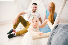 A happy family of three. Mom, dad, child one year old girl in dress play, laugh, smile in bright room. Sunny. Weather Royalty Free Stock Photography