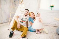 A happy family of three. Mom, dad, child one year old girl in dress play, laugh, smile in bright room. Sunny weather. Family of three people mom with red hair Stock Photos