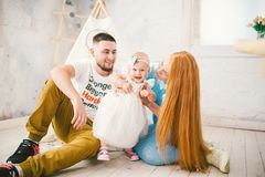 A happy family of three. Mom, dad, child one year old girl in dress play, laugh, smile in bright room. Sunny weather. Family of three people mom with red hair Stock Photography