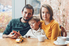 Happy family of three mother, father and son, sitting in restaurant. Portrait of white Caucasian happy family of three mother, father and son, sitting in Stock Image