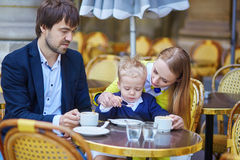 Happy family of three in an outdoor Parisian cafe Royalty Free Stock Photo