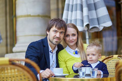 Happy family of three in an outdoor Parisian cafe Stock Image