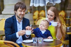Happy family of three in Parisian cafe Royalty Free Stock Photos