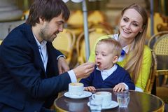 Happy family of three in Parisian cafe Stock Photos