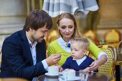 Happy family of three in Parisian cafe Stock Photography