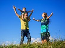 Happy family from three people have fun outdoors. On grass against blue sky Stock Images