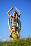 Happy family from three people have fun outdoors. On grass against blue sky Stock Photography