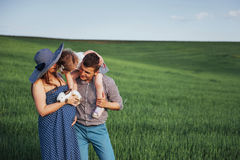 Happy family of three people hugging in the streets Stock Photo