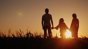 A happy family of three people meets the dawn in a picturesque place. Holding hands royalty free stock photo