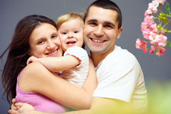 Happy family of three persons embracing. Among flowers Royalty Free Stock Photography