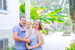 Happy family of three - pregnant mother, father and daughter hugging, laughing, having fun in the sunset park. Family recreation, royalty free stock images