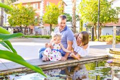 Happy family of three - pregnant wife, father and daughter having fun near pond with water lilies in the park. Family recreation, royalty free stock photo