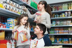 Family of three purchasing food for week. Happy family of three purchasing food for week at supermarket Royalty Free Stock Images