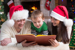 Happy family of three reading book together on Christmas evening Royalty Free Stock Photo