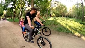 Happy Family Of Three Riding Bicycles In Green stock video