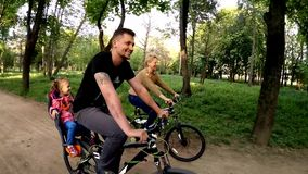 Happy Family Of Three Riding Bicycles In Green stock footage