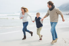 Happy family of three running at beach Royalty Free Stock Image