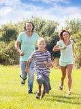 Happy family of three running on grass Stock Photo