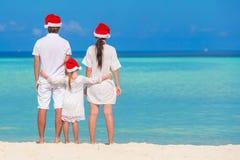 Happy family of three in Santa Hats on beach Royalty Free Stock Photo