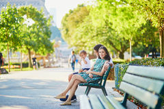 Happy family of three sitting on the bench near the Eiffel tower Royalty Free Stock Photo