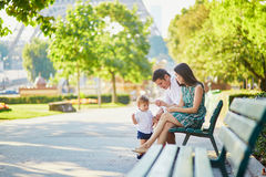 Happy family of three sitting on the bench near the Eiffel tower Royalty Free Stock Photography