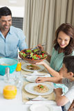 Happy family of three sitting at dining table Stock Image