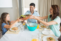 Happy family of three sitting at dining table Royalty Free Stock Images