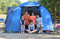 Happy family with three smiling children and tent in summer camp Royalty Free Stock Image