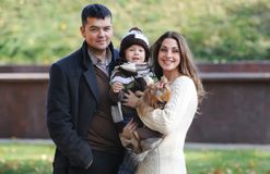 Happy family of three standing together in the park in autumn Stock Photo