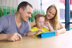 Happy family of three with tablet computer in cafe Royalty Free Stock Images