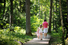 Happy family of three taking a walk in a sunny park Royalty Free Stock Images