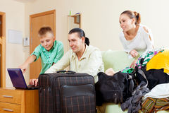 Happy family of three with teenager buying tickets over internet. Happy family of three with teenager buying tickets and packing suitcases for vacation Stock Photos