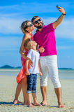 Family of three running along the tropical beach, laughing and enjoing time together. Stock Photography